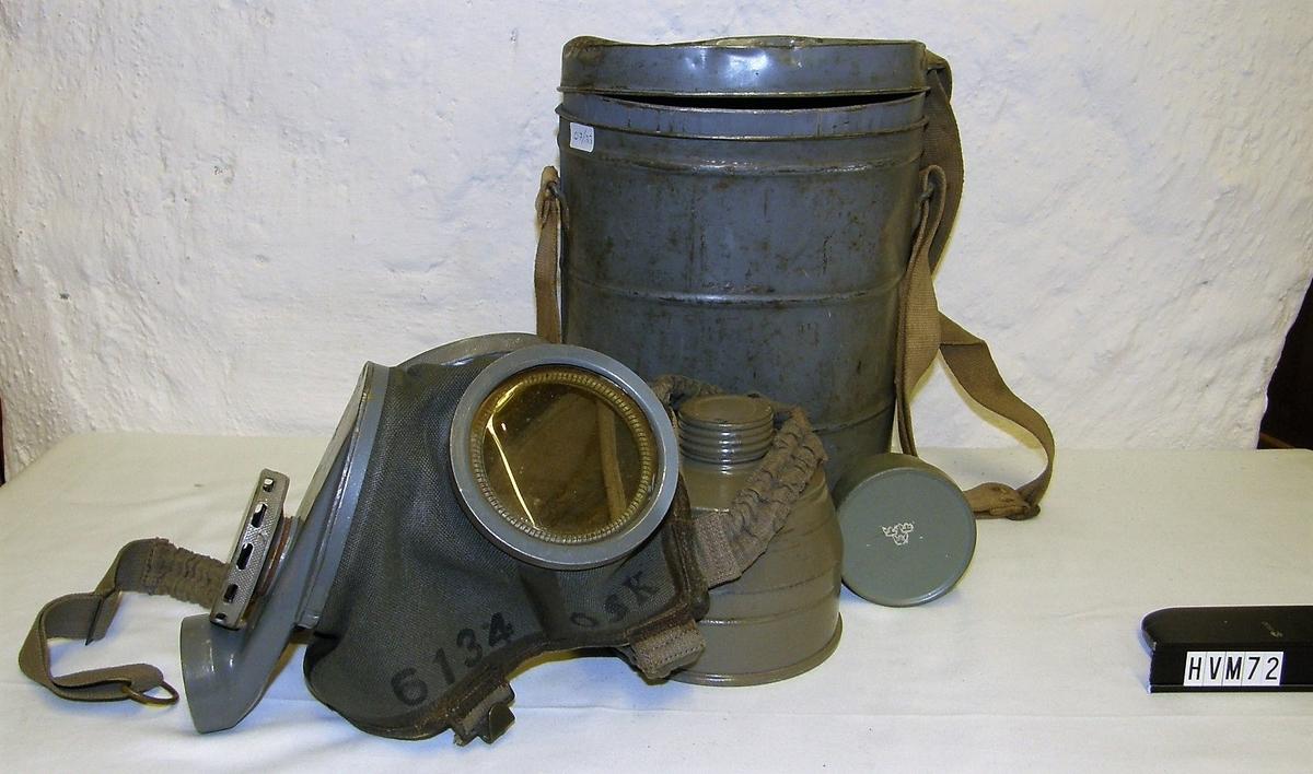 Skyddsmask med tillbehör i plåtbehållare.