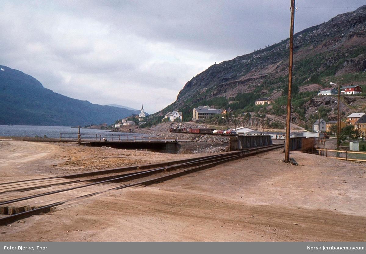 Lomi stasjon med bru over Giken elv og tog som har forlatt stasjonen