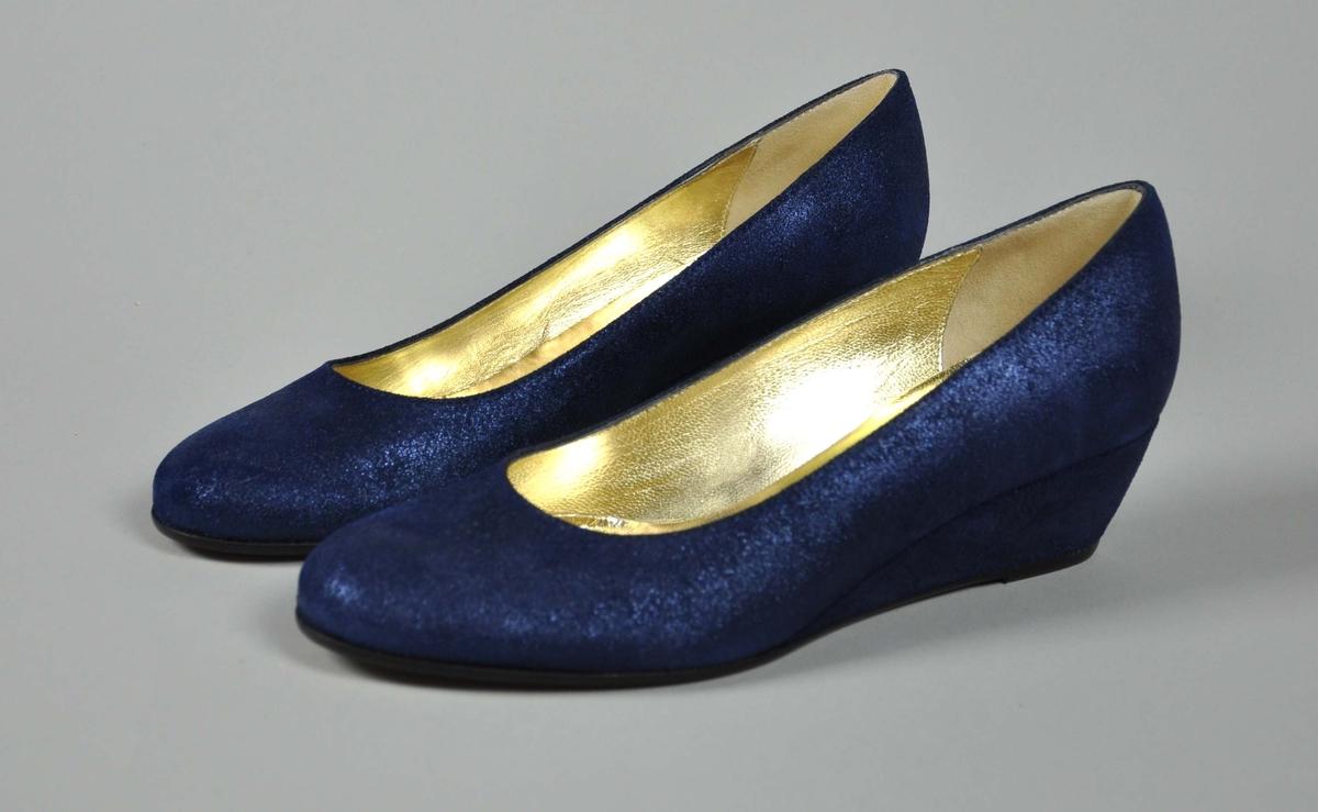 """Et par blå skinn damesko i str.36, """"glinsende""""overflate. Skoene ligger i en svart pose merket Moods of Norway."""