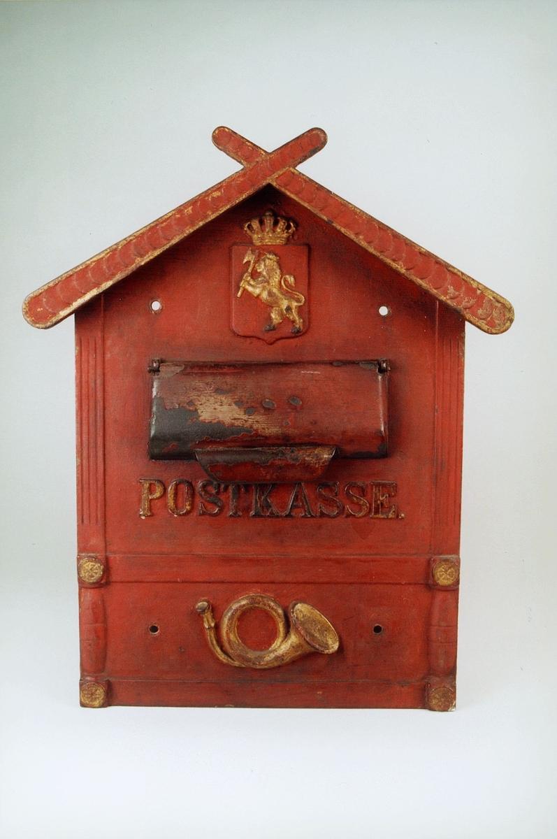 Postkasseskilt av jern for innstikkasse.  Rødmalt med riksløve og posthorn i gult.  Ordet POSTKASSE er støpt inn i kassen. Hull for montering på vegg