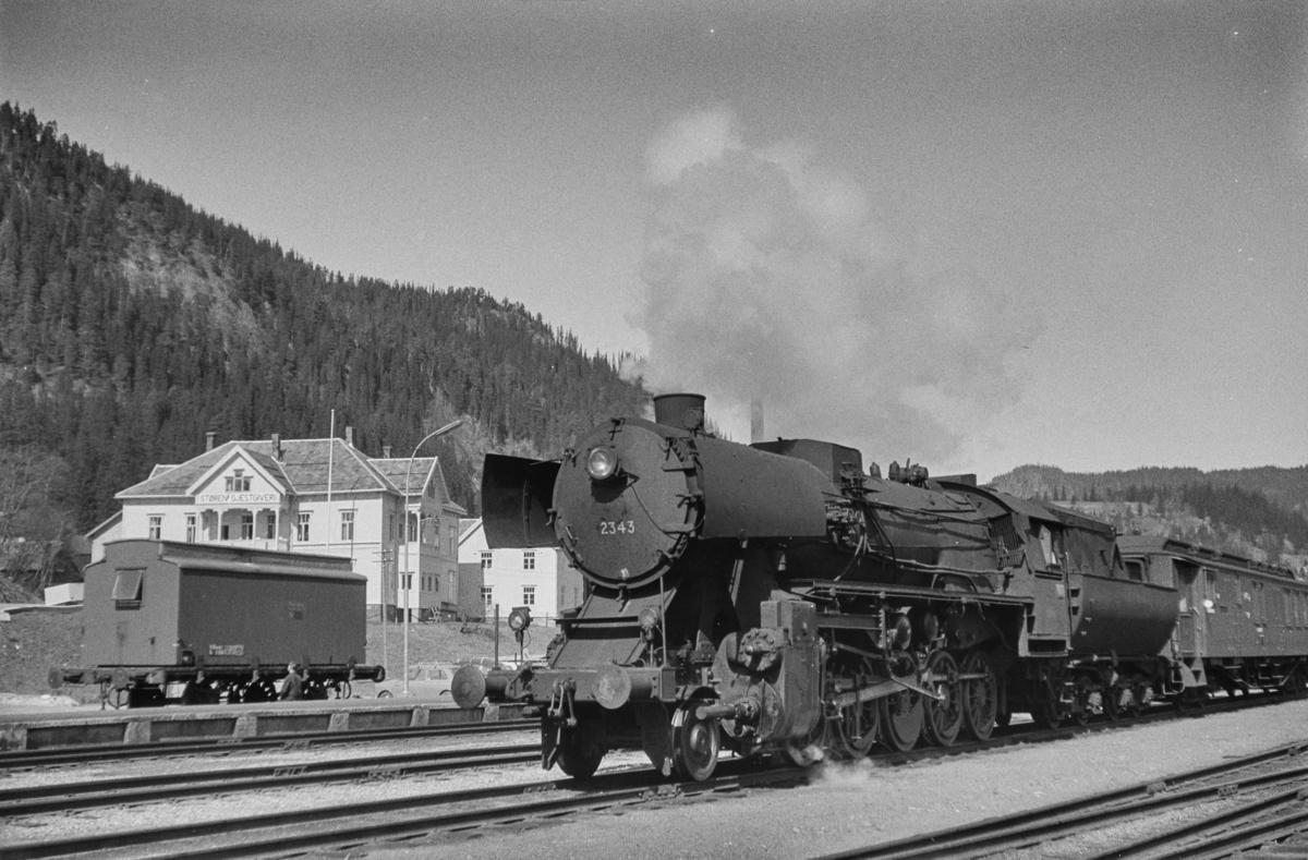 Tog med vogner lastet med pukk på Støren stasjon. Toget er underveis til Dovrebanen. Toget trekkes av damplokomotiv type 63a nr. 2343. I bakgrunnen Støren Gjestgiveri.