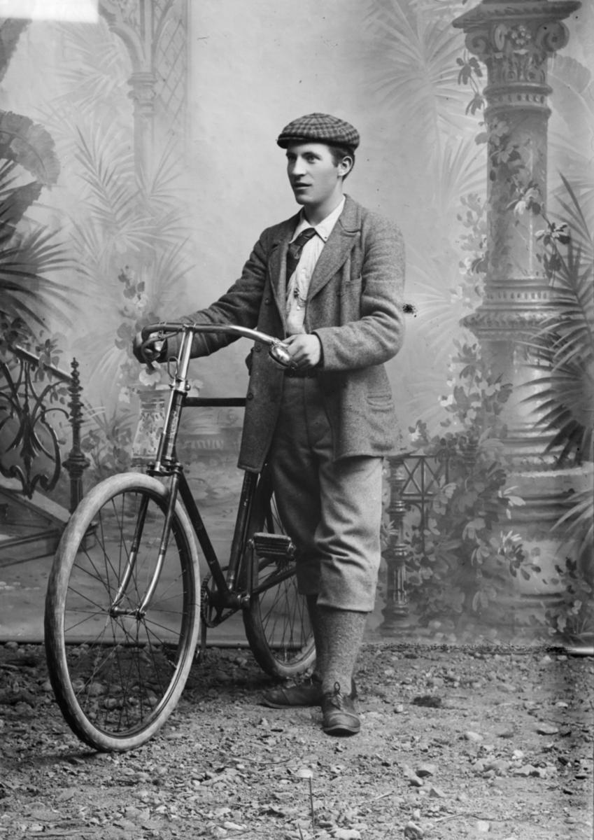 Portrett av Jakob Vangen ved siden av en sykkel