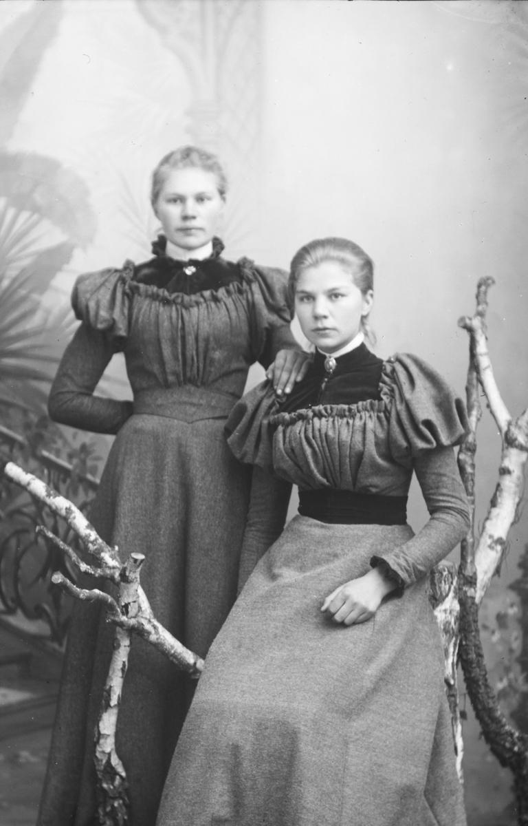 Portrett, to kvinner hvor en sitter på stol, helfigur. Til venstre Ragnhild Skurdal, med søster.