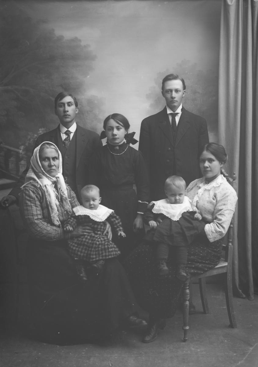 Gruppe. Robert Brøste med familie: Voksen kvinne med småbarn, yngre kvinne med småbarn, ung jente, to voksne menn