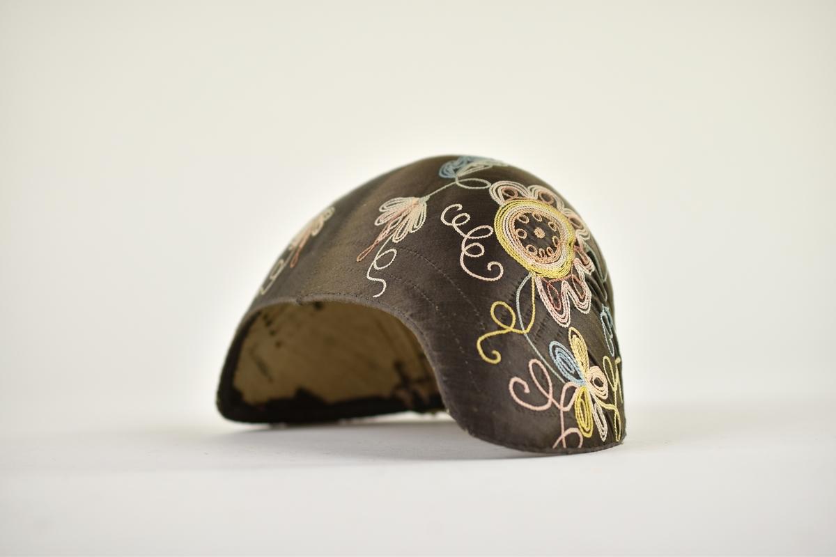 Brun bindmössa i siden. Dekorerad med broderi i kedjestygn i form av blommor i olika färger.