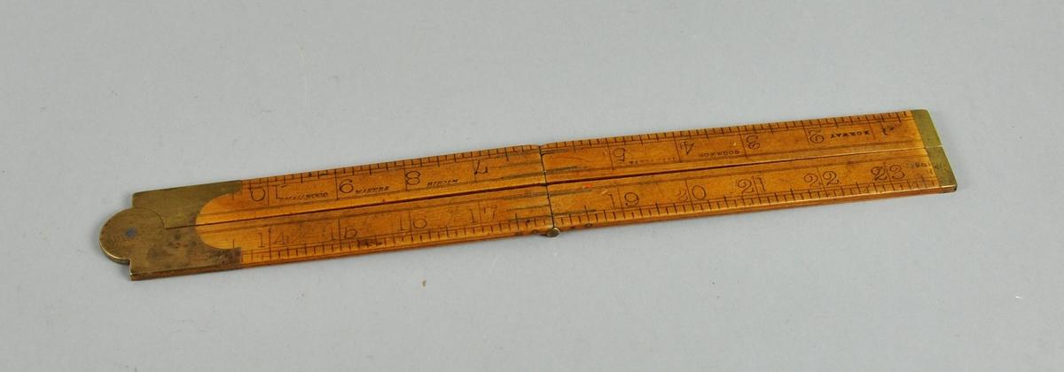 Sammenleggbar tommestokk av tre og metall med både cm og tomme som måleenheter.