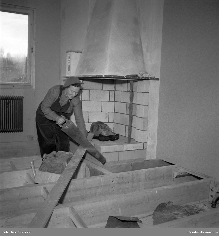 Husbyggande fru i Nacksta. En kvinna och en katt vid ett villabygge på Sallyhillsvägen 69.