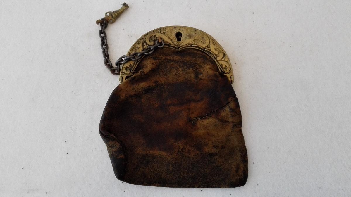 Form: Pung med lås av messing og nøkkel av jarnkjatting. Støypte ornament (ranke) på låset.