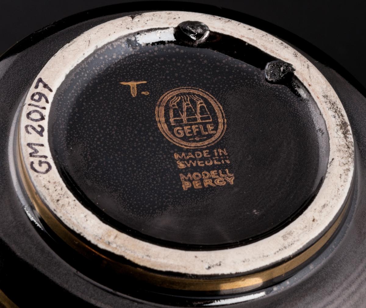 """Vas av flintgods, formgiven av Arthur Percy för Gefle Porslinsfabrik, modell -AQ. Rund, konisk nedåt. Räfflad på tvären. Rund fotring. Handmålad. Dekor, guldfärgat rutmönster i upplösning på utsidan mot svart glasyrfond. Dekor 207. Guldfärgad skorstensstämpel under med text """"Gefle Made in Sweden modell Percy"""" samt singerad """"T."""""""