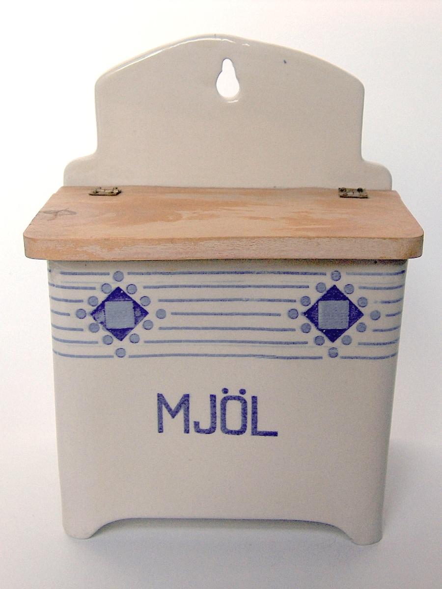 """Mjölkar i flintgods, Gefle Porslin. Raka väggar, förlängt bakstycke med upphängningshål, trälock. Dekor: blå, band av ränder med snedställda kvadrater med ytterligare kvadrater inuti, prickar. Text: """"Mjöl"""". Modell: Orsa."""
