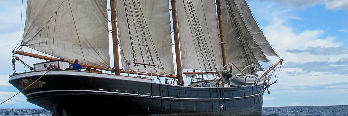 """Skonnerten """"Svanen"""" med tre master og for fulle seil ute på vannet, sett fra styrbord."""
