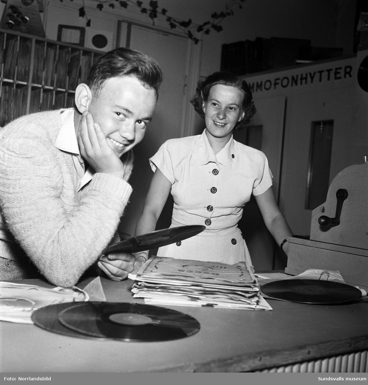 Två bilder från en skivaffär i Sundsvall med grammofonskivor uppsatta på en skärm. I bakgrunden på den andra bilden syns två stycken grammofonhytter där kunderna kunde provlyssna på skivorna.