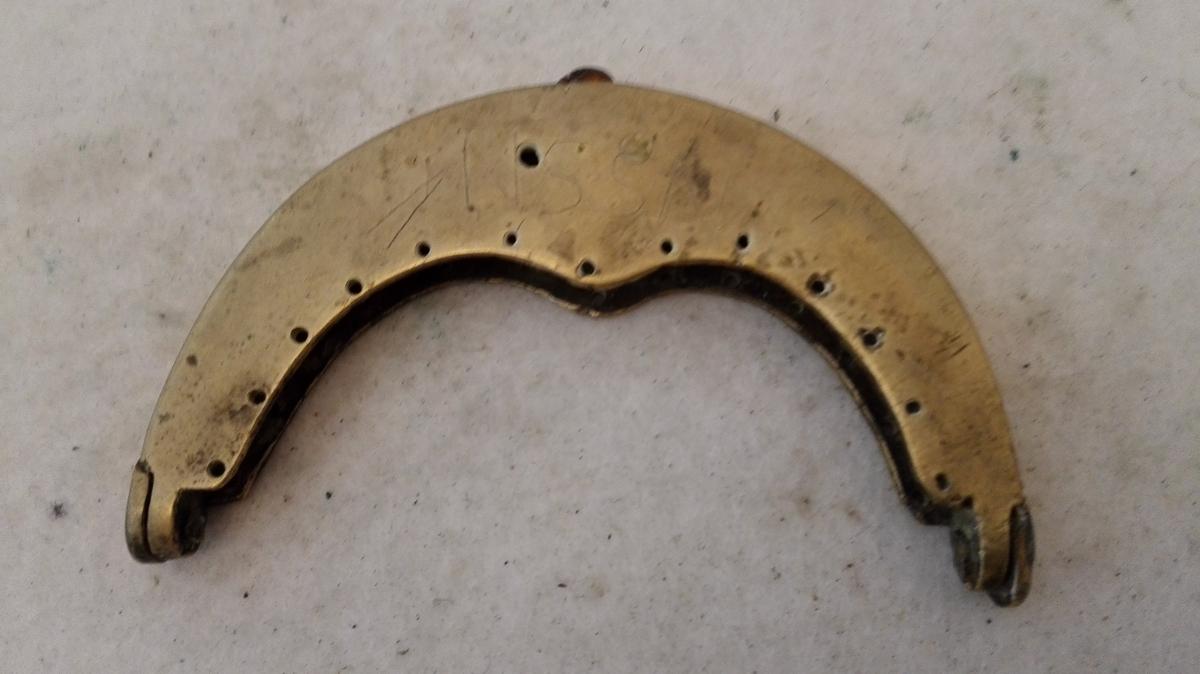 1 messing pungelaas.  Glat messing pungelaas, 9,6 cm bredt. Paa den ene side indridset NSSN.  Kjöpt av landhandler Th. Lindström, Lærdal.