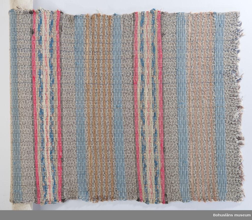"""Mönster av ränder i skilda bredder; bomullstrasor och klippt skarpsillsvadduk. Fiskegarnstrasor till vävning kallades dialektalt för fläckefiller. Vartannat inslag av bomullstrasor, vartannat av fiskegarnstrasor. Man använde kasserade bitar av bl.a. skarpsillsvadduk och av makrillgarn för att dryga ur bomullstrasorna. Mattan fick därigenom en jämnare färgskala, men nackdelen var att mattorna blev litet """"vissnare"""", låg inte så stadigt på golvet som när de var vävda enbart av bomullstrasor. Att väva bottnarna, alltså mellan bårderna av endast garn eller vad var därför inte speciellt populärt. Man kallade ofta bårderna för """"ränder"""".  Angående trasmattor med fiskgarnsinslag, berättat av Folke Larsson, museiföreståndare på Kosters hembygdsförening, för Ann-Marie Brockman, Bohusläns museum, i augusti 2005: Man rullade ihop det uttjänta fiskegarnet till en lång, smal rulle. Med yxa högg man 3 centimeter breda bitar ur rullen. Dessa drogs ut på längden - man hade då rejält långa bitar att använda som inslag i väven.  Uppgifterna kompletterade 2005-10-07."""