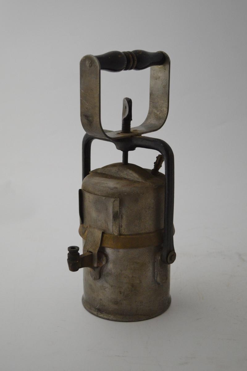 Arbeidslampe, karbidlampe. Håndholdt, sylindrisk from. Mangler reflektor.