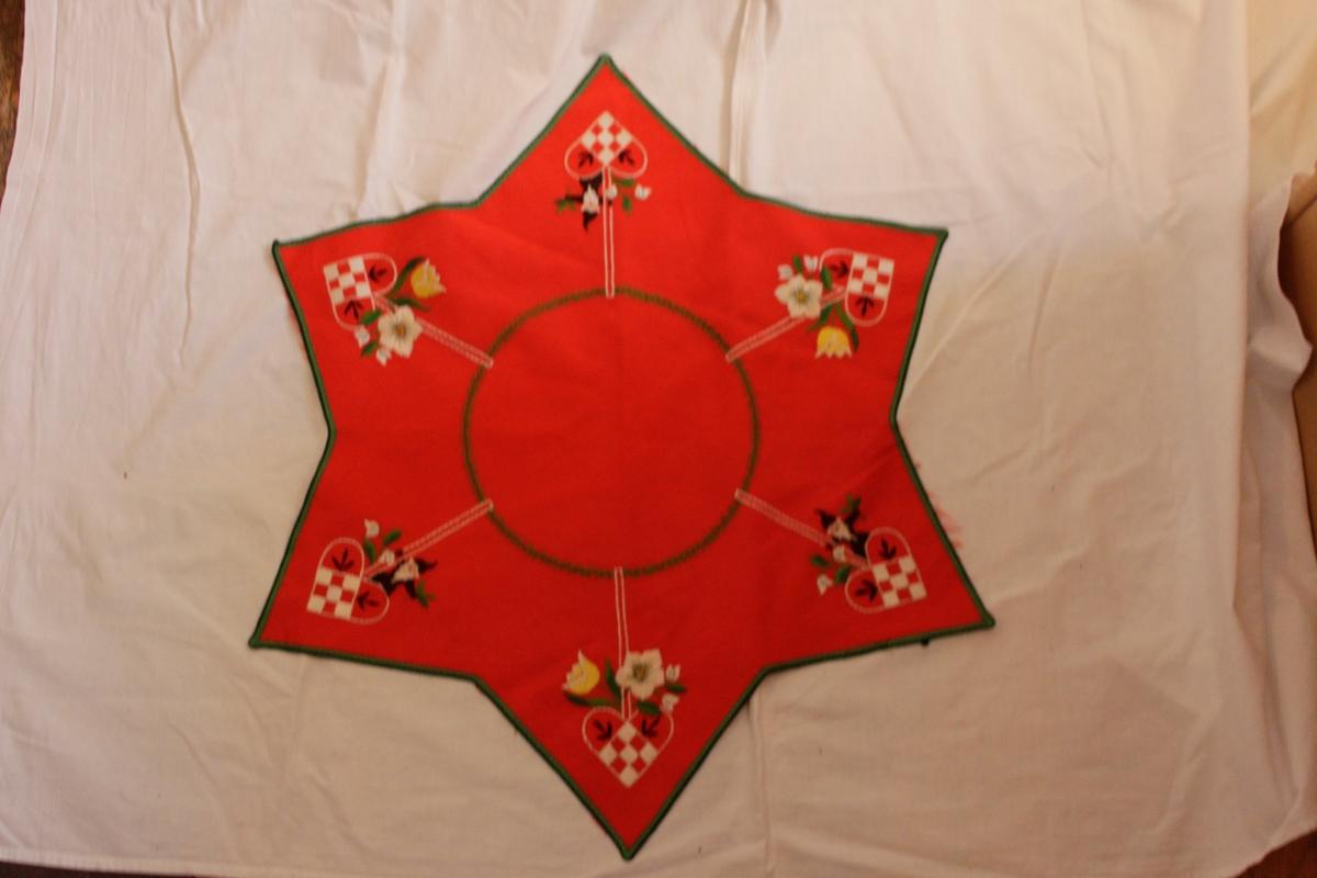 Röd prydnadsduk i bomull, broderad. Stjärnformad julduk med grön kant broderade blommor, tomtar, fläthjärtan samt en granrisgirland. Sömnadstekniker: plattsöm och stjälkstygn.