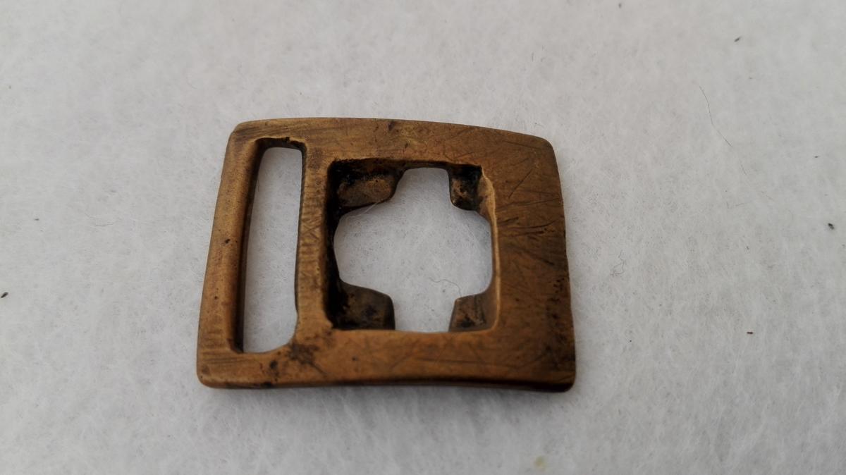 Form: Sokkeband av skinn med massingbeslag. Sokkebaandsbeslag av messing   Et sokkebaand av skind med messingbeslag samt 2 stykker messingbeslag til sokkebaand av sk ind, den ene forsirt paa oversiden med indstemplete ringer. Kjøpt av Erik Stubben, Jostedal ved K.A. Ormbergstøl (Sjå kat. nr. 3508). G.F.H.