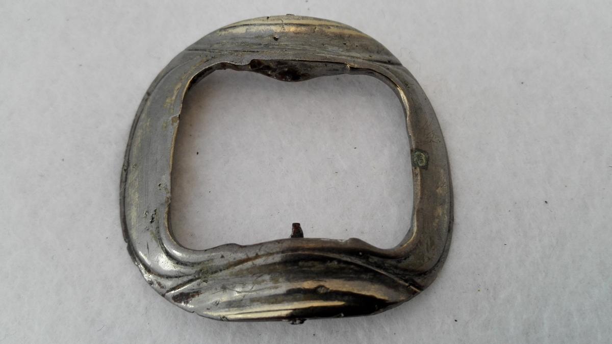 1 skospænde av tin.  Stöpt tin (haard legering) skospænde, defekt, idet tanden mangler.  Kjöpt av landhandler Theodor Lindström, Lærdal.