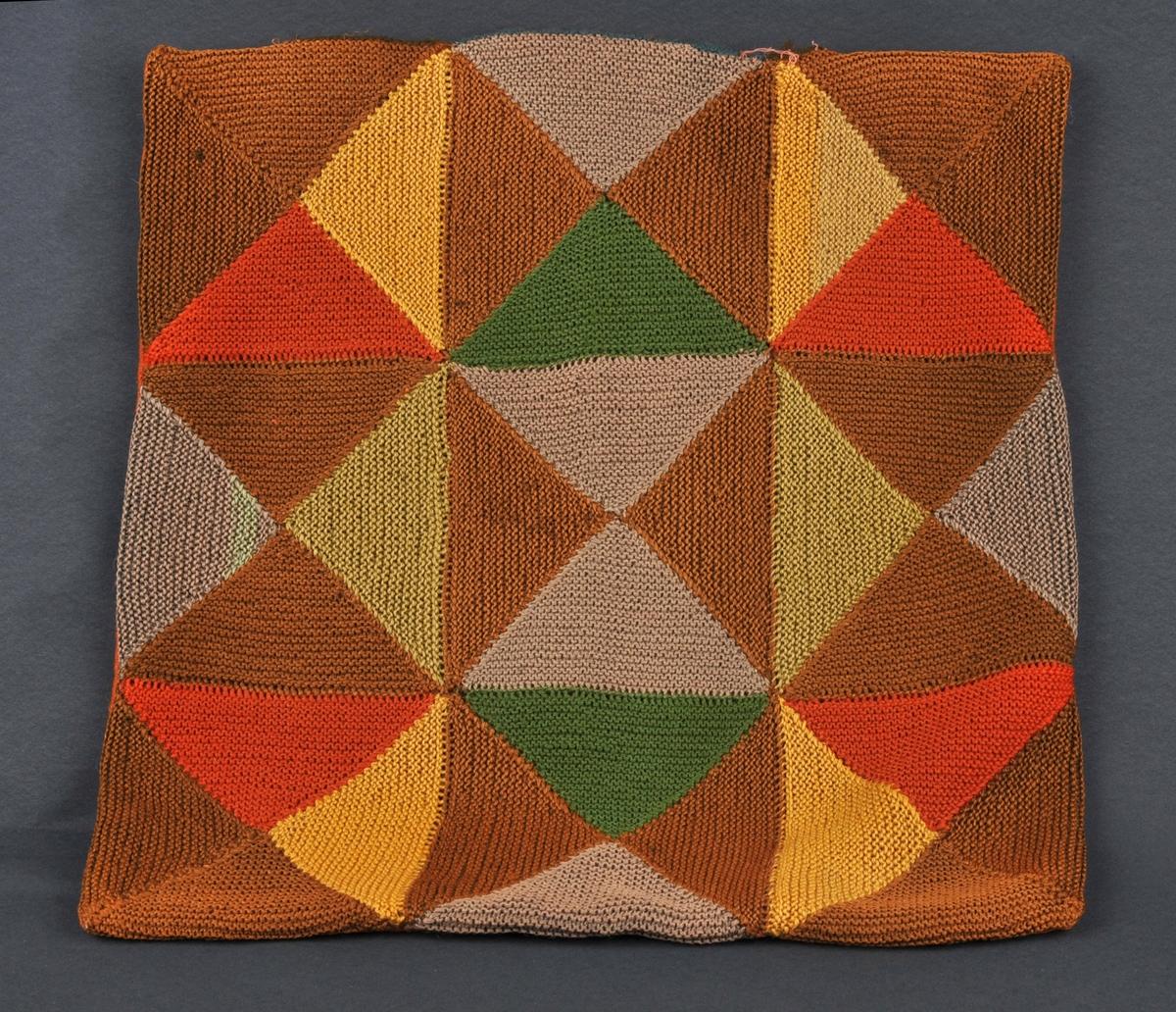 Oversida er sett saman av rettstrikka trekantar. Baksida er av rustfarga ulltøy.