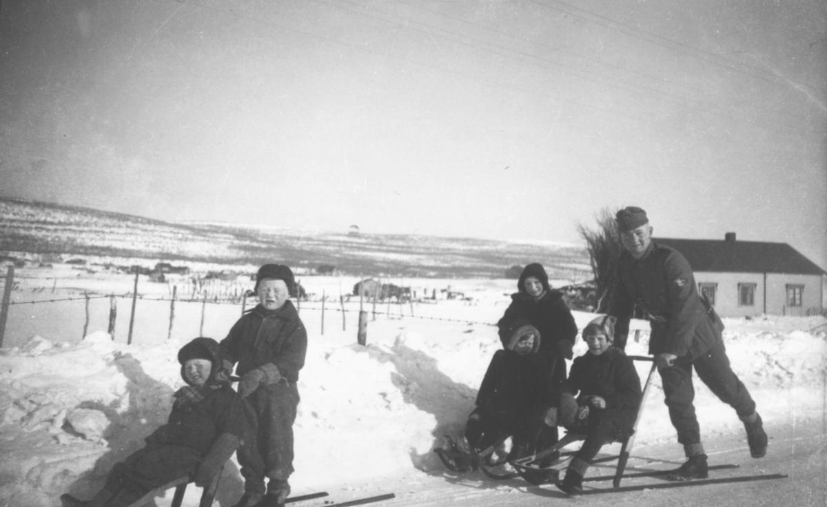 Tysk soldat Matthias Schlagwein avbildet sammen med barn fra Vestre Jakobselv på sparkstøtting 1940-1941.