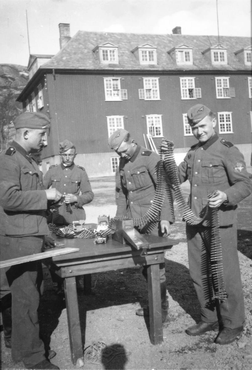 Fire tyske soldater i Kirkenes. Mattias Schlagwein selv til høyre. En haug med patroner ligger på bordet ute ved garnisjonskompanihuset. Schlagwein viser frem en patronbelte.