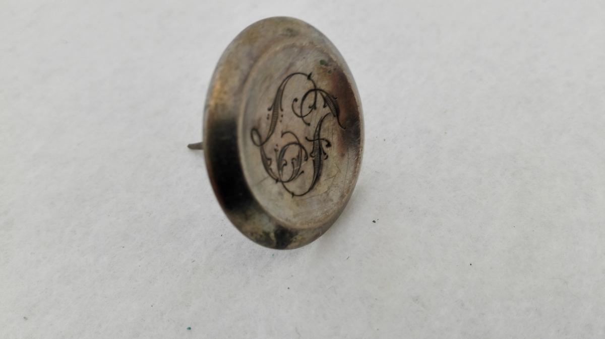 Form: Rund, kuva med markert kant og graverte  initial sentrert i knappen. Pålodda nål vertikalt på knappehovudet. Laura Faleide var mor til gjevar og gift med lensmann Andreas Faleide.