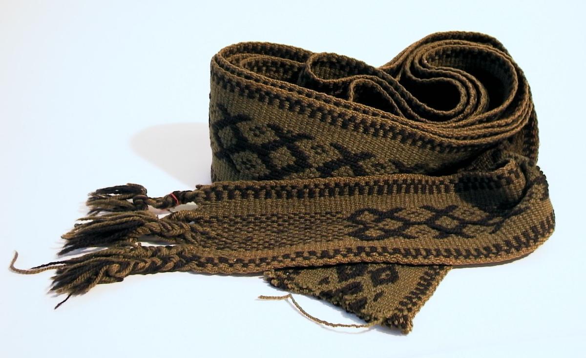 Pälsband av ullgarn med plockat mönster. Grön bottenfärg med mönstertrådar i svart.