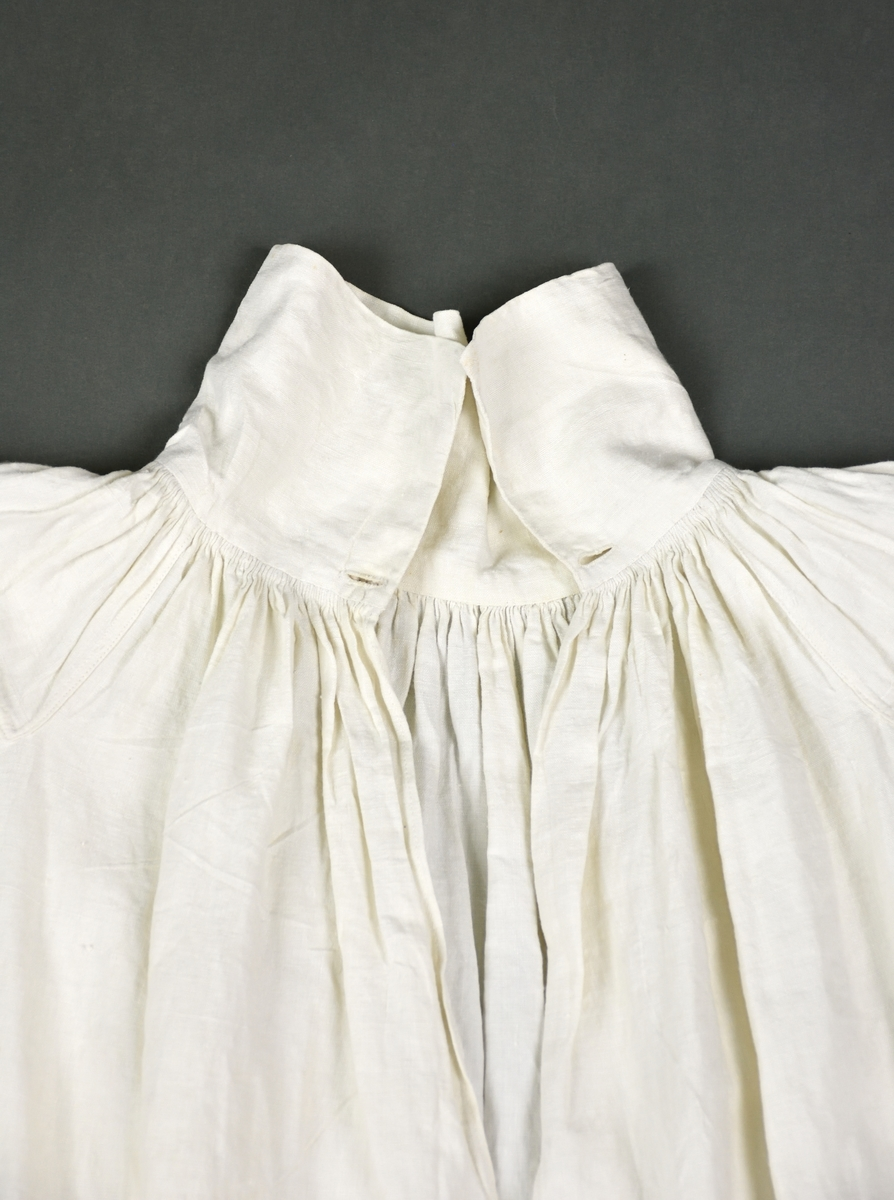 Skjorta av linnelärft med hals och ärmspjäll. Skjortans krage är utan broderier. Ärmlinningarna har en smalbård av rätlinjig plattsöm samt fina rynkor. Plagget knäpps med en brun metallknapp i halsen.