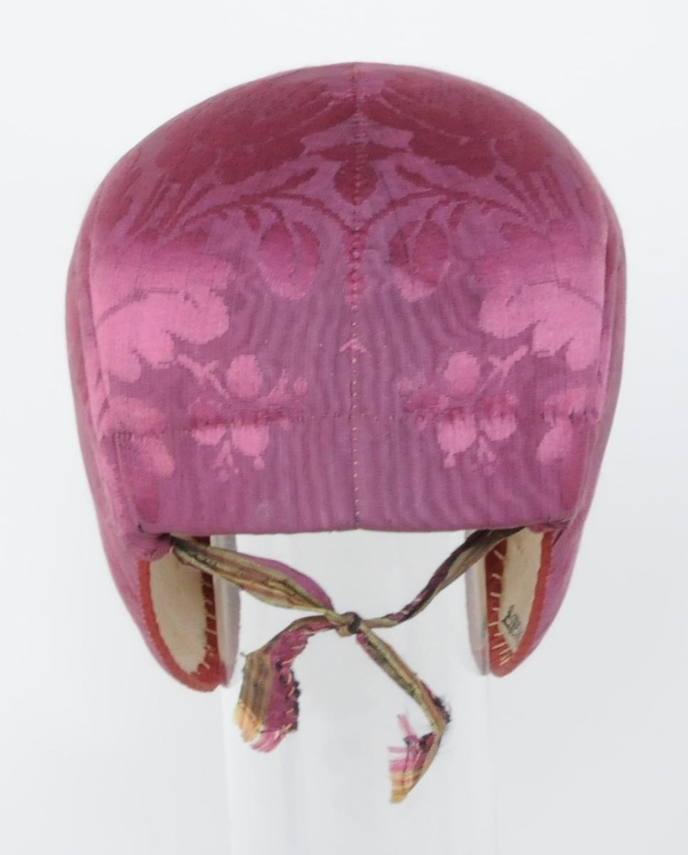 Rosa/violett bindmössa med lösspets, broderad på bomull.