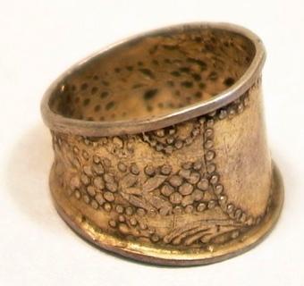 Fingerring med upphöjda kanter av förgyllt silver. Ringen har ett utvidgat framstycke med en slät sköldformad platta. På ringens sidor finns dekoration av pressad vegetativ ornering.