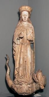 Krönt helgonskulptur föreställande sankta Margareta. Helgonet har långt hår och håller en röd bok i sin vänstra hand. Hon bär en förgylld mantel med blå insida över en tunika med bälte.