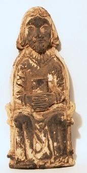 Reliefartad sittande manlig bild, med händerna sammanknäppta kring en bok i knät. Polykromi borta. Troligen från predikstol.