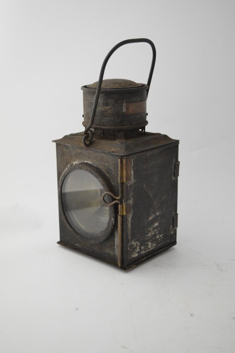 Håndholdt parafinlampe med festemulighet. Kubisk, rektangulær hovedform med et hvitt og ett rødt glass i hver side, flatt glass, ikke buet linse. En luke kan åpnes på en tredje side for å tenne lampen. Sylinderformet topp.