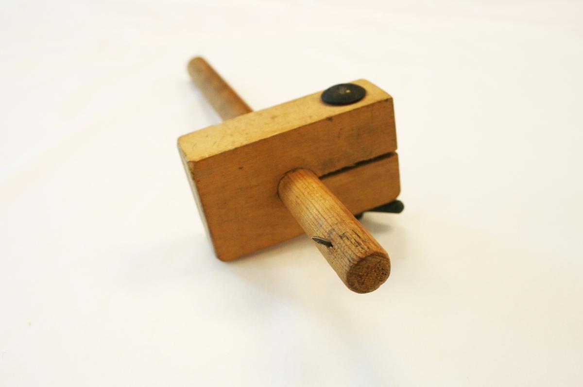 Stekmål i tre. Pinne med spiker i den ene enden, en kloss er festet med en liten tvinne og bolt i metall til å kunne justere avstanden fra markeringspinnen (spiker).