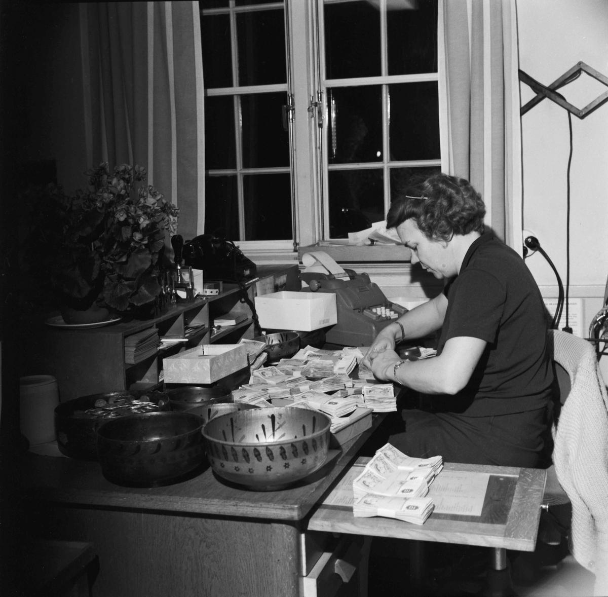 Skansens julmarknad 1966. Kvinna räknar pengar.