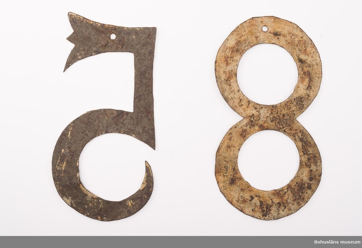 2 psalmnummersiffror av vitmålad järnplåt.  5, 8. UM005660:055-056.  Ur handskrivna katalogen 1957-1958: Trälåda m. siffror för psalmnummer 1-8: Bly. H.: 16 cm, m. utsirningar 9-19: Bly. H.: 9 à 10 cm; m. utsirningar. 20-28: Bly o mässing. H.: 15 cm. 29-31 Bly H.: 13 cm. 32-42: Bly o mässing. H.: 10 cm. 43-51: Bly o mässing. H.: 7 cm. 52-54: Gjutna av gulmetall. H.: 10 cm. 55-56: Vitmålad järnplåt. 57: Bly. H.: 10,5 cm.  Lappkatalog: 13