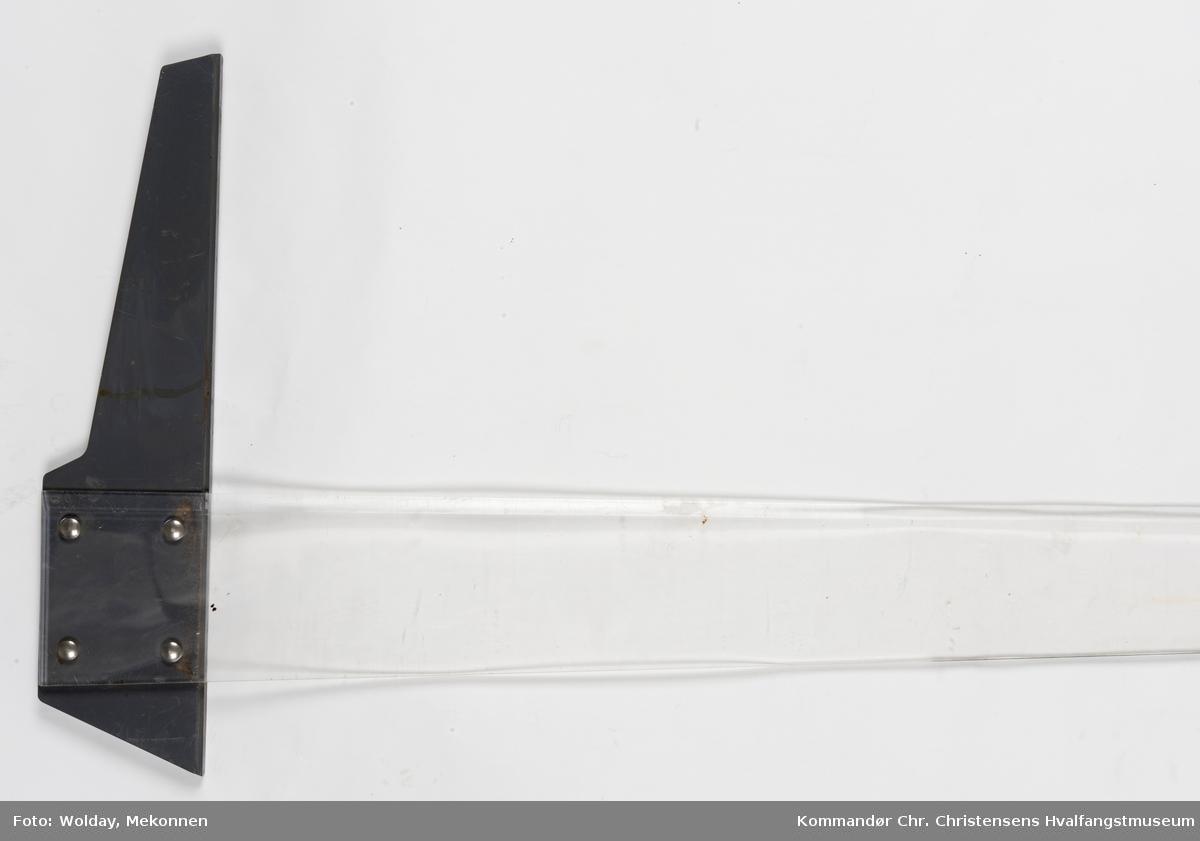 Form: T-form, lang linjal med cm-skala. Rundt hull i enden