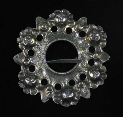 Glibbsølje i sølv med forgylt forside. Bunnskiva er drevet og har seks ansiktsmasker hver omgitt av en rosett bestående av seks drevne skåler. Rosettene gir inntrykk av oppsatt hårpynt. Mellom hver maske skyter bunnskiva ut i en tungeformet flik. Fra basis utgår vifteformet strekdekor. Bunnskiva er noe oppbøyd mot sentrum, hvor tornhullet er omgitt av en ring dannet av skruetråd. Partiet nærmest ringen er fylt med skjellignende gravyr som stort sett begrenses av en konsentrisk anbrakt hullsirkel. Se Rikard Berge pl. XLII for lignende sølje.