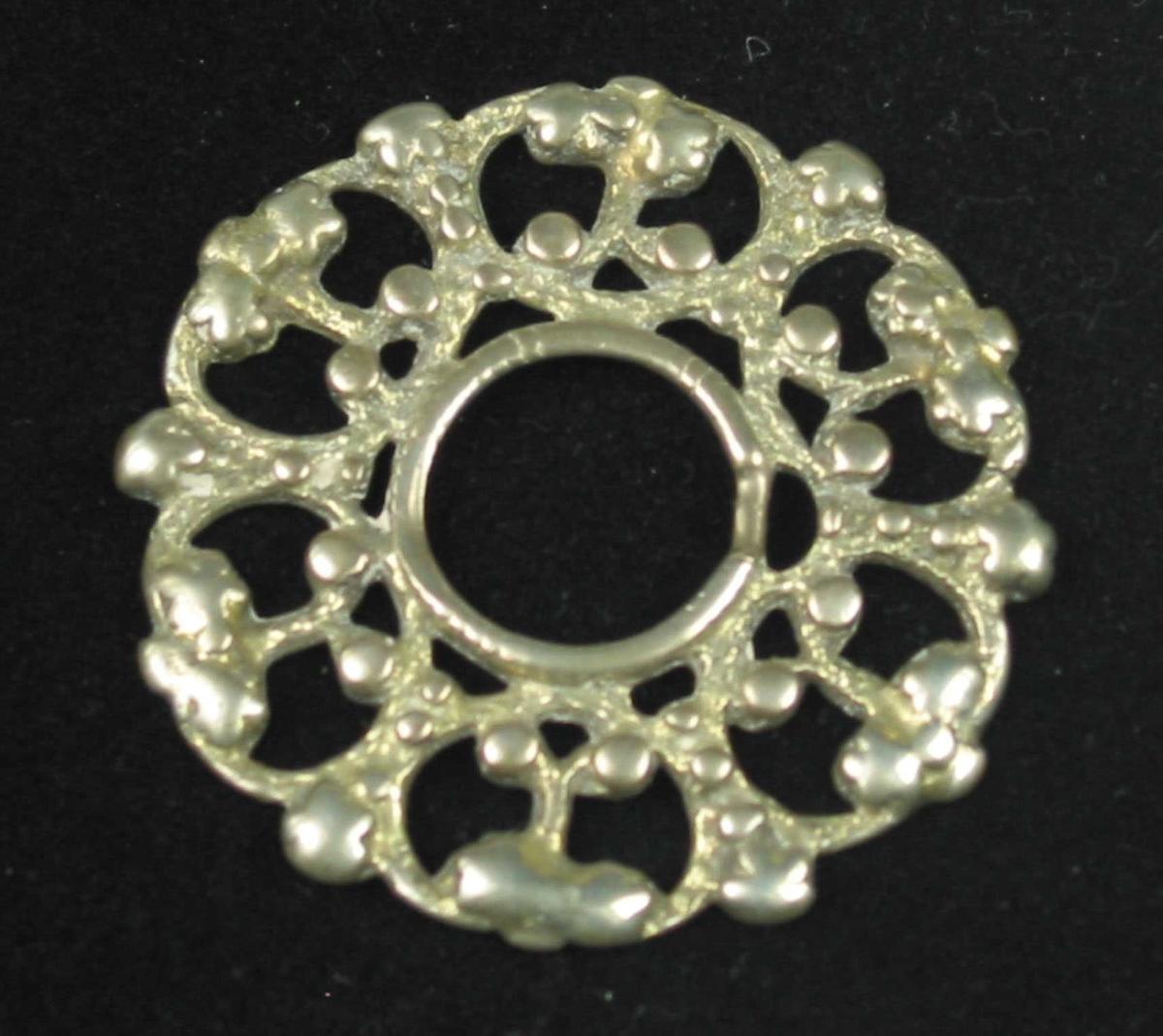 Støpt rosesølje i sølv med forgylt forside. Bunnen er svakt kuvet og består av seks bladnyrer med ryggen innad og festet til tornringen. Bladringene møtes i en stolpe inne i bladnyret og og deler seg i to henimot nyreveggen, hvor endene er festet. Alle bladhjørnene og skillene mellom nyrene er utfylt med knopper eller fem-delte rosetter. Tornringen er meget slitt, men skal forestille en ring av skruestråd. Hovedkatalogen beskriver en torne av messing. Denne er nå borte.
