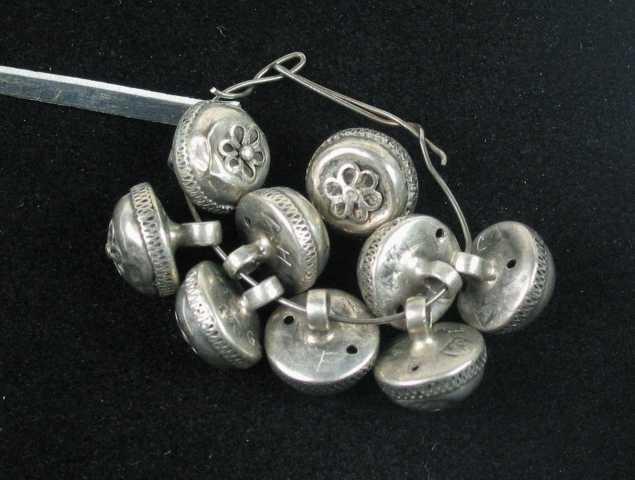 Ni knapper i sølv. De er halvkuleformet med svakt buet bunn der hekteløkka er festet. Nederst på bolen har den en krage som ligner pipene på en prestekrage. På toppen er det en dobbel seks-løkket trådrosett med perle. Løkkene har en glatte ytterst med skruetråd innenfor. Knappen er hul.