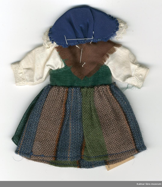 KLM 28082:62. Dockdräkt, dam, av textil, ylle, siden, sammet och linne. Dräkten består av kjol, förkläde, väst, skjorta, schal och huvudbonad. Nationaldräkt från: Rödön, Östersund, Jämtland.