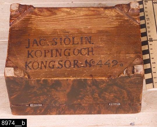 """Anmärkningar: Schatull, Jacob Sjölin, 1780-1788.  Gångjärnsförsett rektangulärt lock med raka kanter. På locket finns ett handtag i mässing. Undertill försett med rester av Köpings hallstämpel (jämför bild 21542__b) samt """"JAC. SIÖLIN. / KÖPING och / KONGSÖR: No 449."""" (bild 8974__b). På fronten finns en hjärtfomad nyckelskylt i mässing. Invändigt är schatullet försett med mönstrat papper bild 8974__c). Fyra konturerade fötter. H:105 Br:175 Dj:120  Hela schatullet är fanerat med alrot, blindträet är furu. Schatullet är tämligen väl hållet. I synnerhet är den mörka ytbehandlingen, som har gjort Sjölin berömd, i bra skick.  Mälardalen och framför allt städerna Arboga, Köping, Kungsör och Eskilstuna var under 1700-talets senare hälft och början av 1800-talet centrum för tillverkning av alrotsfanerade möbler och föremål. Här tillverkades bl.a. fällbord, byråar och olika sorters askar. Föremålen såldes inte bara inom mälardalen utan även till Stockholm och till andra länder. Det främsta namnet inom alrotsföremålsproduktionen är Jacob Sjölin (1737-1785). Alroten togs inte från alens rötter utan från stamansvällningar vid rötterna. I synnerhet vid Mälarens stränder har tillgången på detta sorts virke varit god. På slottet förvaras en kortkatalog, upprättad av f.d. antikvarie Carin Thorsén. Den upptar över 300 alrotsföremål tillhörande museer, privatpersoner etc.  Jacob Sjölin (1737-1785), gick i lära hos Jonas Nordling i Arboga. Sjölin blev mästare under hallrätten i Köping och Kungsör 1767 och kvarstod som mästare intill sin död 1785. Ungefär 2000 föremål tillverkades i hans verkstad. Sjölins speciella ytbehandling (fernissa) på möblerna gav dem en särskild glans och hållfasthet. Ingen mästare i Sverige har överträffat Sjölin i framställandet av alrotsfanerade möbler. Sjölin använde sig av tre olika brännstämplar, av Åke Nisbeth klassificerade som typ A, vilken är äldst men också använd under hela Sjölins livstid och även efter hans död, mellan 1785-1788 då verkstaden drevs"""