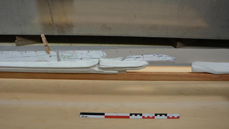 Nærbilde av 3D-printede kjøldeler i hvit plast montert på treramme. Et av kjølbordene i papp er også montert på babord side av kjølen.