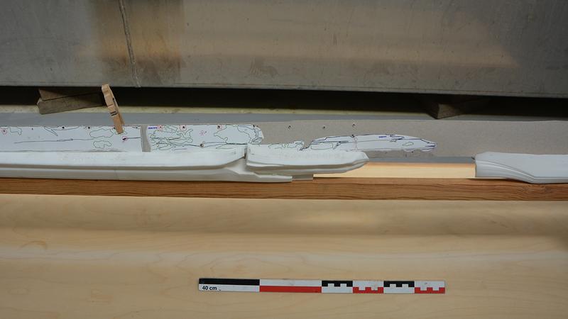 Nærbilde av 3D-printede kjøldeler i hvit plast montert på treramme. Et av kjølbordene i papp er også montert på babord side av kjølen. (Foto/Photo)