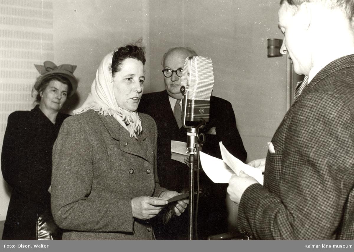 Radiointervju programledare intervjuar en gäst åhörare i kulissen.