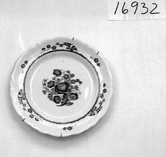 """Anmärkningar: Tallrik av flintporslin. Rörstrand. Servis Särö. Dekor på brätte och spegel. Blå på gråvit bottenglasyr. Vågat brätte. Glasyren nött på ett parti av brättets ytterkant. F. ö. skadat. Rörstrand 1926-1929. Märke Särö, Rörstrand kronstämp. Stämplar O. Rörstrand H 28, Z9. """"Märta och Karl Adolphsons samling."""""""