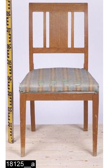 Anmärkningar: Stol, Karl Johan modell, 1900-tal.  Rakt överstycke. Svagt svängda bakstolpar. Genombruten rygg med en rektangulär ryggbricka och två ryggspjälor samt en ryggslå. Stoppad sits med randigt tyg. Samtliga ben är utåtsvängda från stolen (bild 18125__b). H:860 Br:465 Dj:460  Hela stolen är betsad.  Tillstånd: Tyget är skadat. Samtliga fotavslutningar är slitna. Betsen har försvunnit på ett flertal ställen.  Historik: Gåva från Fröken Eva Karlssons, Västerås, dödsbo 1974 enligt testamente. Enligt kortkatalogen tillverkad av Sköld & Karlsson, Västerås. Ingår i möblemang 18124-18132.