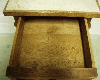 Anmärkningar: Kommod. Trä. Perstorpsplatta. Kommoden består av en skåpdel och en låddel, mellan dessa två finns fyra runda profilerade och kannelerade pelare. Lådan och skåpets dörr är fanerade. Bägge har släta speglar med profilerade lister. Låddelens skiva utbytt mot en träskiva med perstorpsplatta.