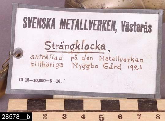 """Anmärkningar: Klocka, enligt uppgift en """"Strängklocka"""", 1800-tal.  Böjt fäste med integrerad klocka och bjällra. På fästet sitter en lapp med texten """"SVENSKA METALLVERKEN, Västerås Strängklocka, anträffad på den Metallverken tillhöriga Myggbo Gård 1921"""" (bild 28578__b). H:175 L:230  Historik: Gåva från SAPA AB, Division Service, 2002. Föremålet stod i ett skyddsrum på bruksområdet i Skultuna."""