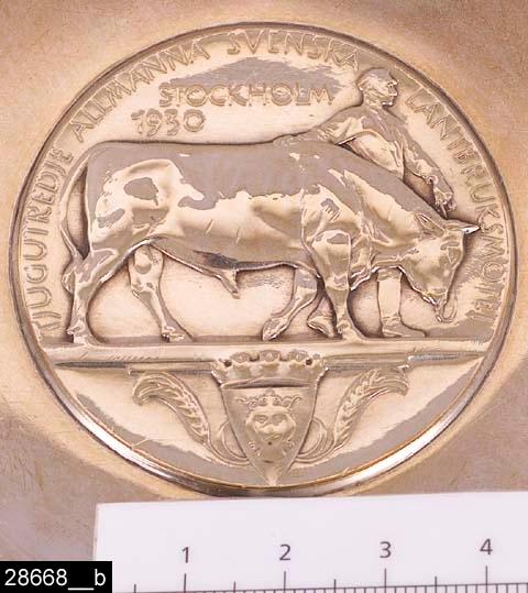 """Anmärkningar: Skål på fot, 1930.  Rund skål på fot med dekorerad innerkant i form av axdekorer. I mitten är ett mynt inslaget föreställande en man, en ko samt Stockholms skyddshelgon S:t Erik. På myntet finns texten """"TJUGOTREDJE ALLMÄNNA SVENSKA LANTBRUKSMÖTET STOCKHOLM 1930"""" (bild 28668__b). På foten finns silverstämplar bl.a. en tillverkarstämpel (Borgila) samt en årsstämpel (D8) vilket betecknar år 1930. Stämplarna är mycket svåra att se och går inte att fotografera. Runt foten finns en text som lyder """"AKTIEBOLAGET KALK-IMPORTS HEDERSPRIS"""". H:65 D:225  Tillstånd: Nyskick.  Historik: Gåva från SAPA AB, Division Service, 2002. Föremålet stod i ett skyddsrum på bruksområdet i Skultuna."""